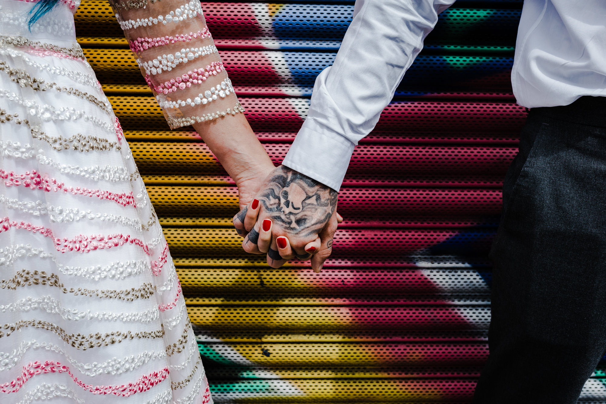Small Weddings - Couple holding hands in front of graffiti wall