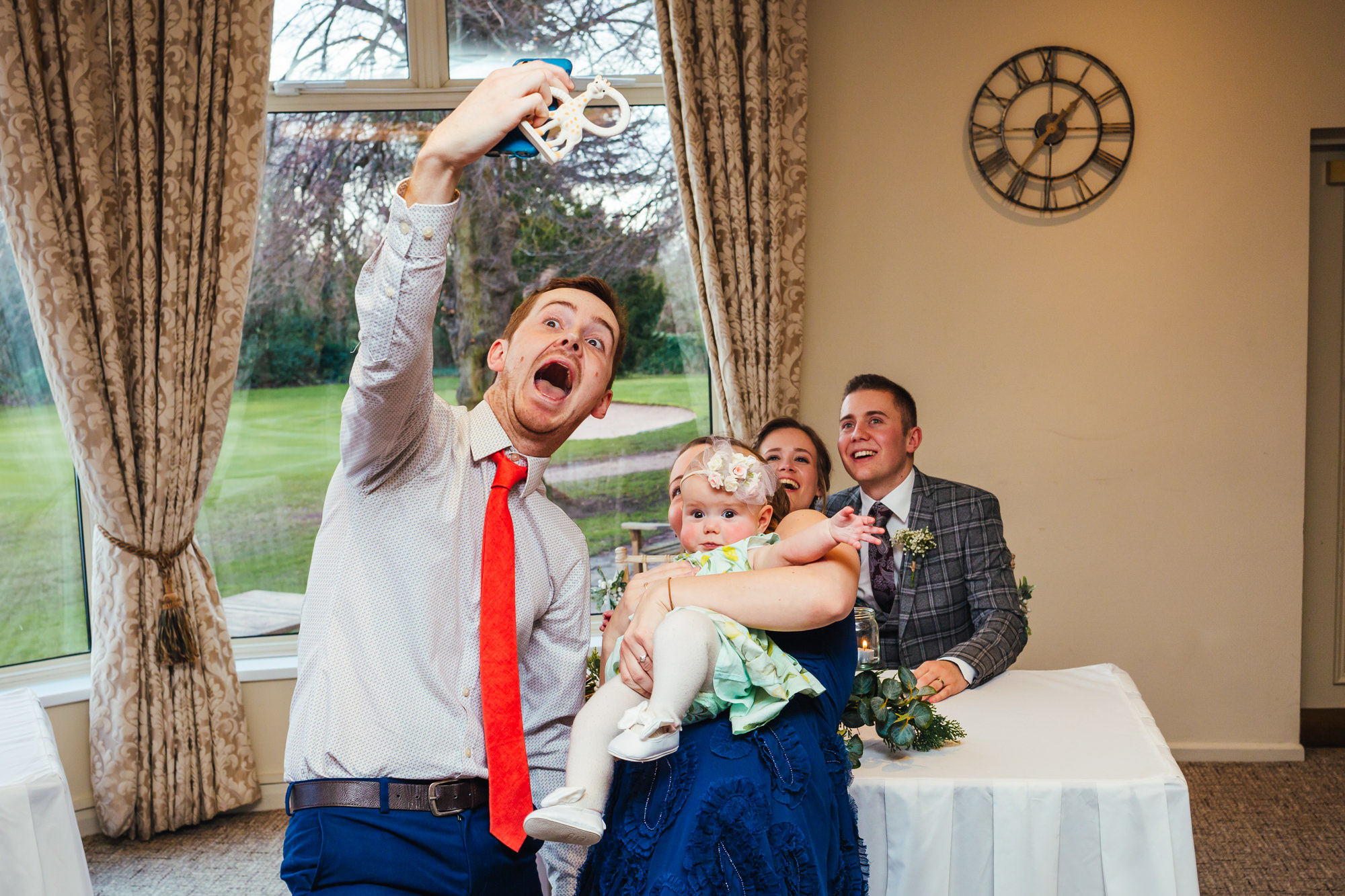 Wedding Photography Nottingham - Couple taking selfie with baby in front of bride and groom during ceremony