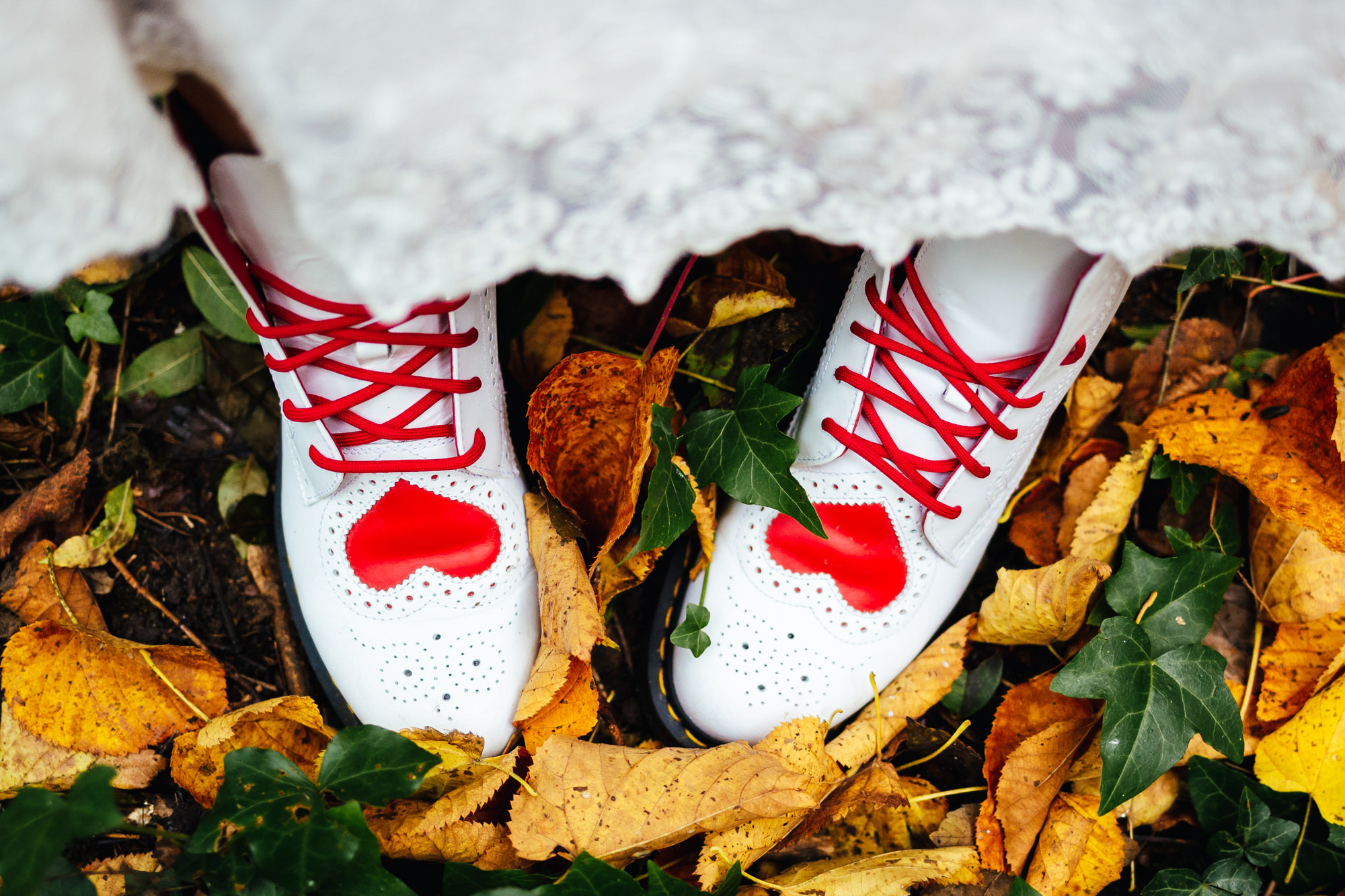 Being yourself on your wedding day - Alternative wedding shoes, doc martens with love hearts on a leafy background