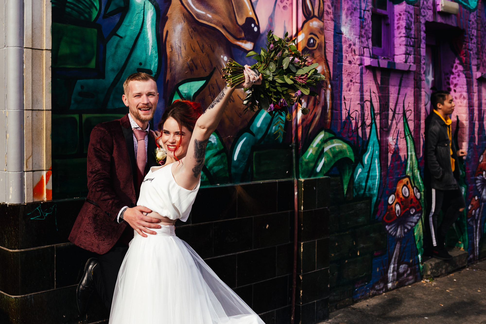 Being yourself on your wedding day - Couple stood in front of a graffiti wall in Camden Market