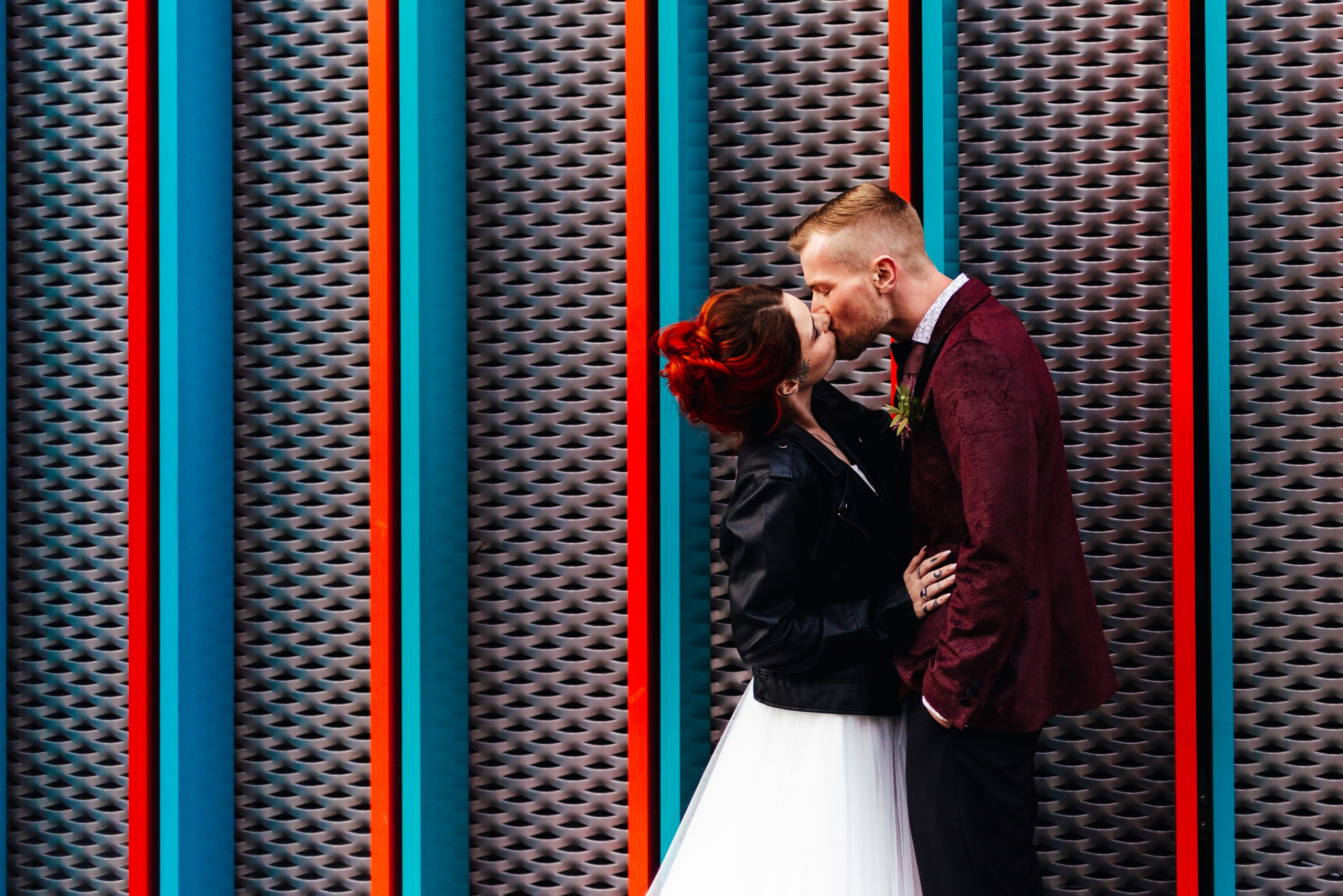Choosing Your Wedding Photographer - Couple stood in front of colourful wall in Camden Town kissing