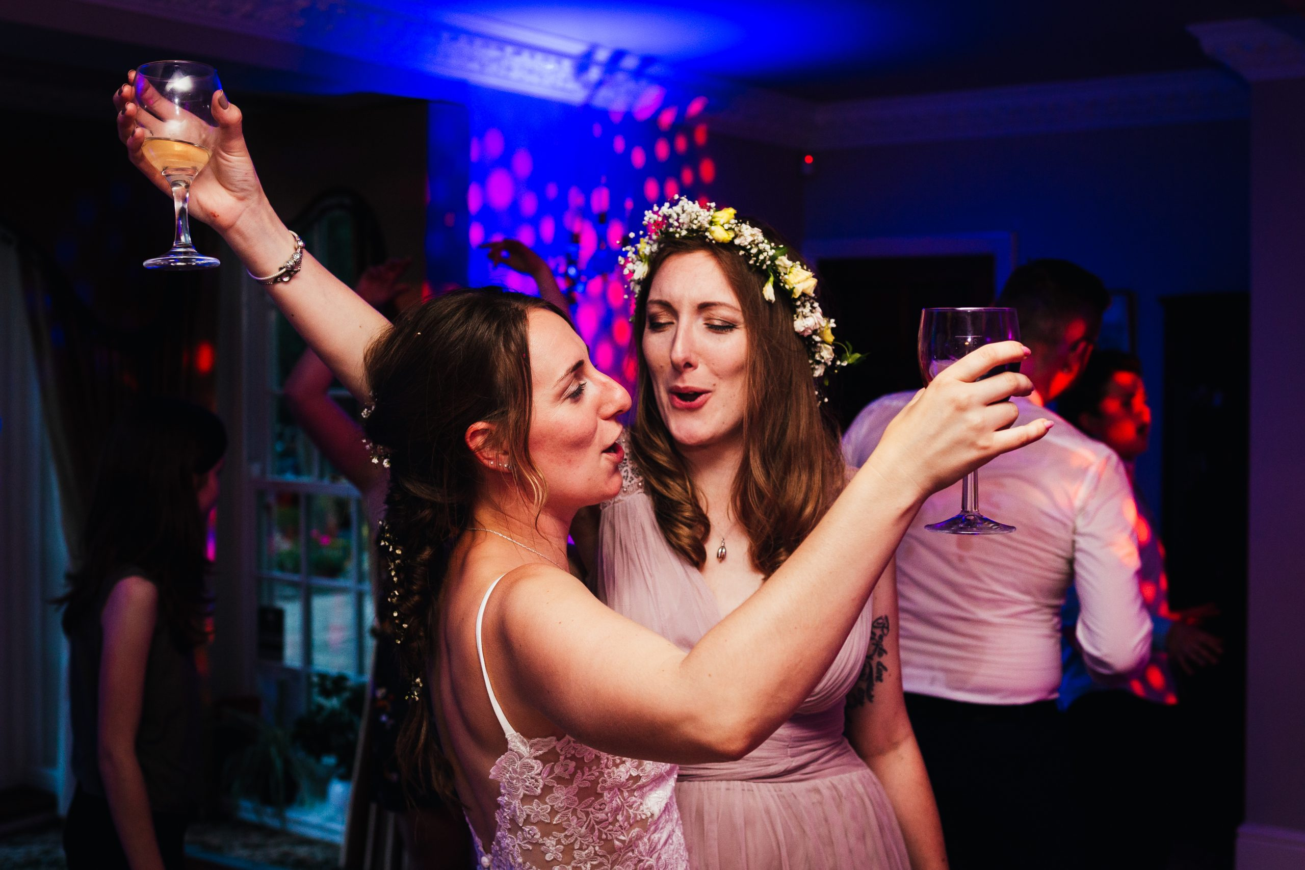 Choosing Your Wedding Photographer - Bride and bridesmaid dancing at wedding reception with wine glasses raised