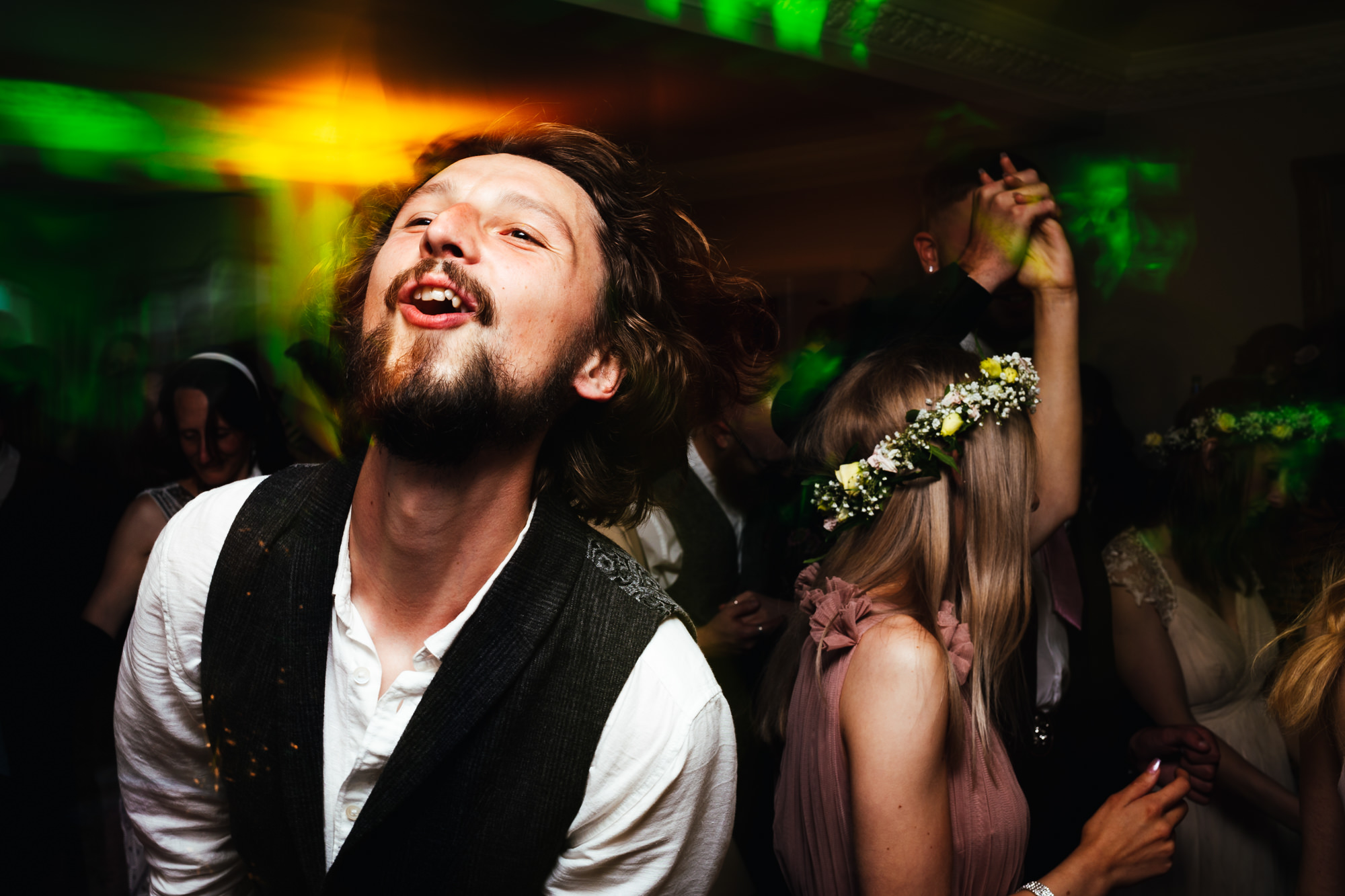 Wedding Photography Nottingham - Guy busting out some moves on wedding dance floor backed by green and yellow lights