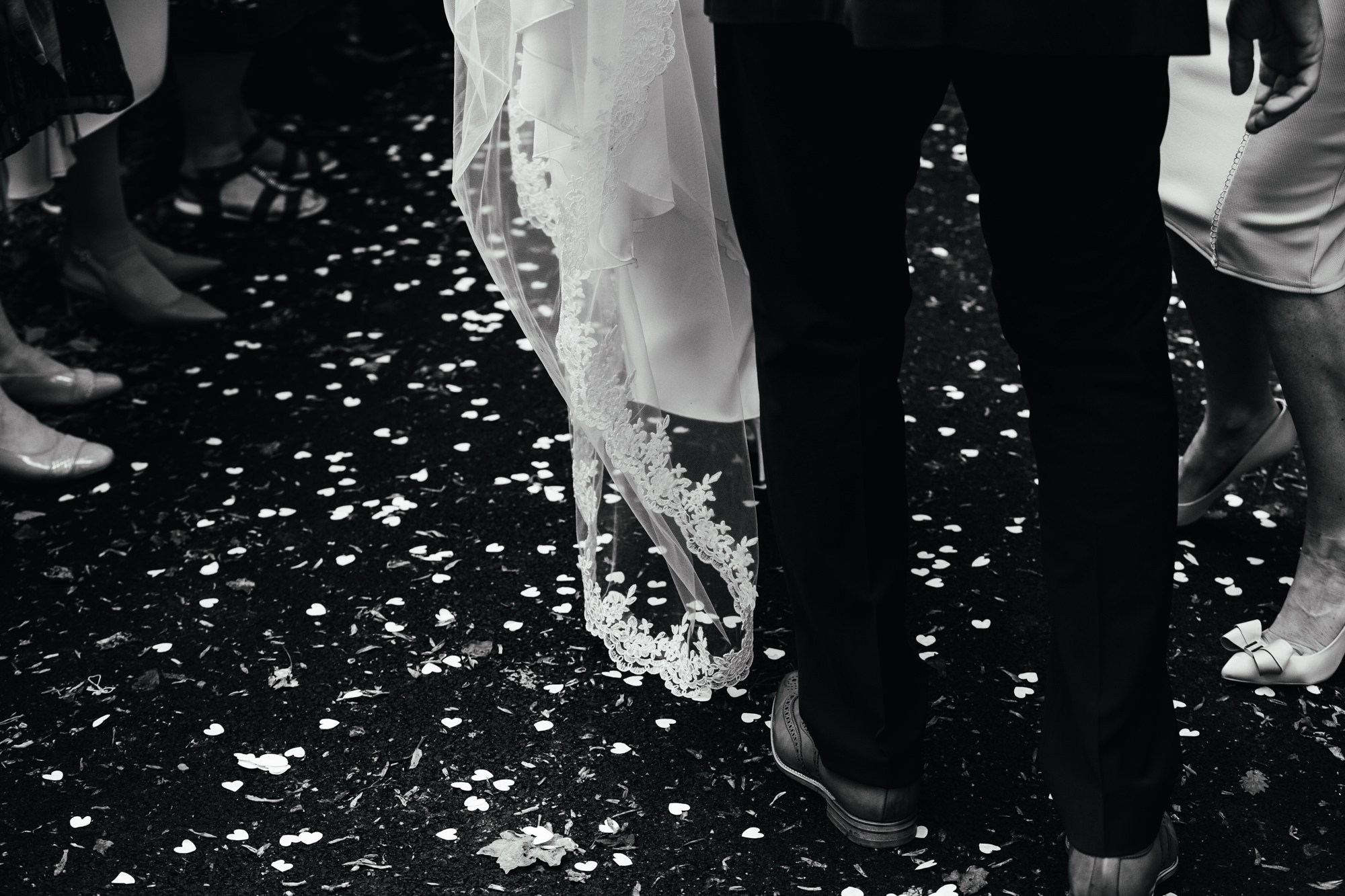 Second Wedding Photographer - Couple walking through confetti after wedding ceremony. Picture is in black and white