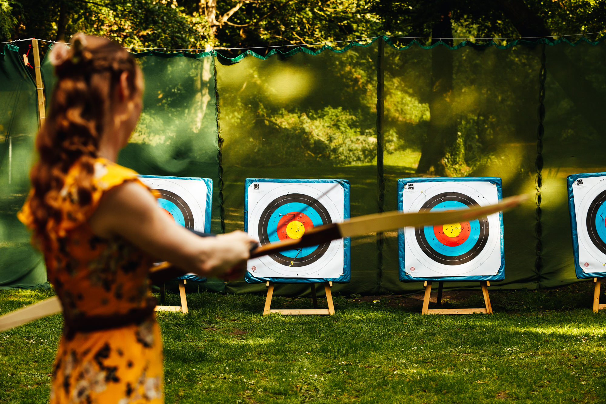 Relaxed Wedding - Games for guests, archery is a lot of fun here is a woman shooting an arrow