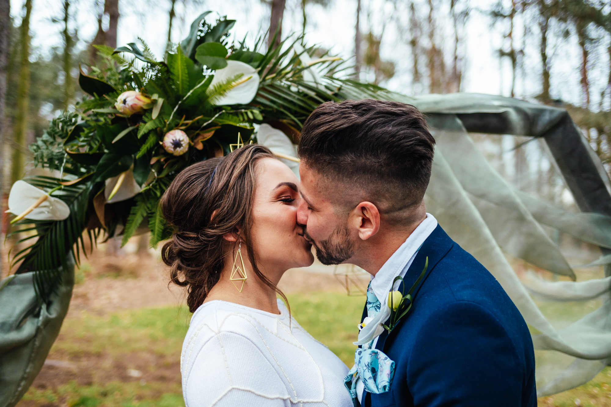 Relaxed Wedding - Couple kissing in front of backdrop at outdoor ceremony
