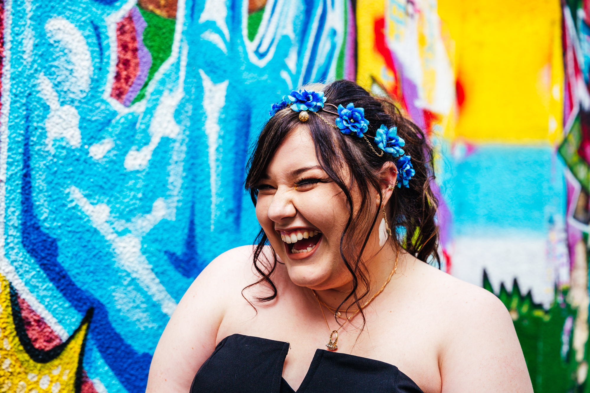 Small Wedding - Bride smiling widely on her wedding day in front of colourful wall