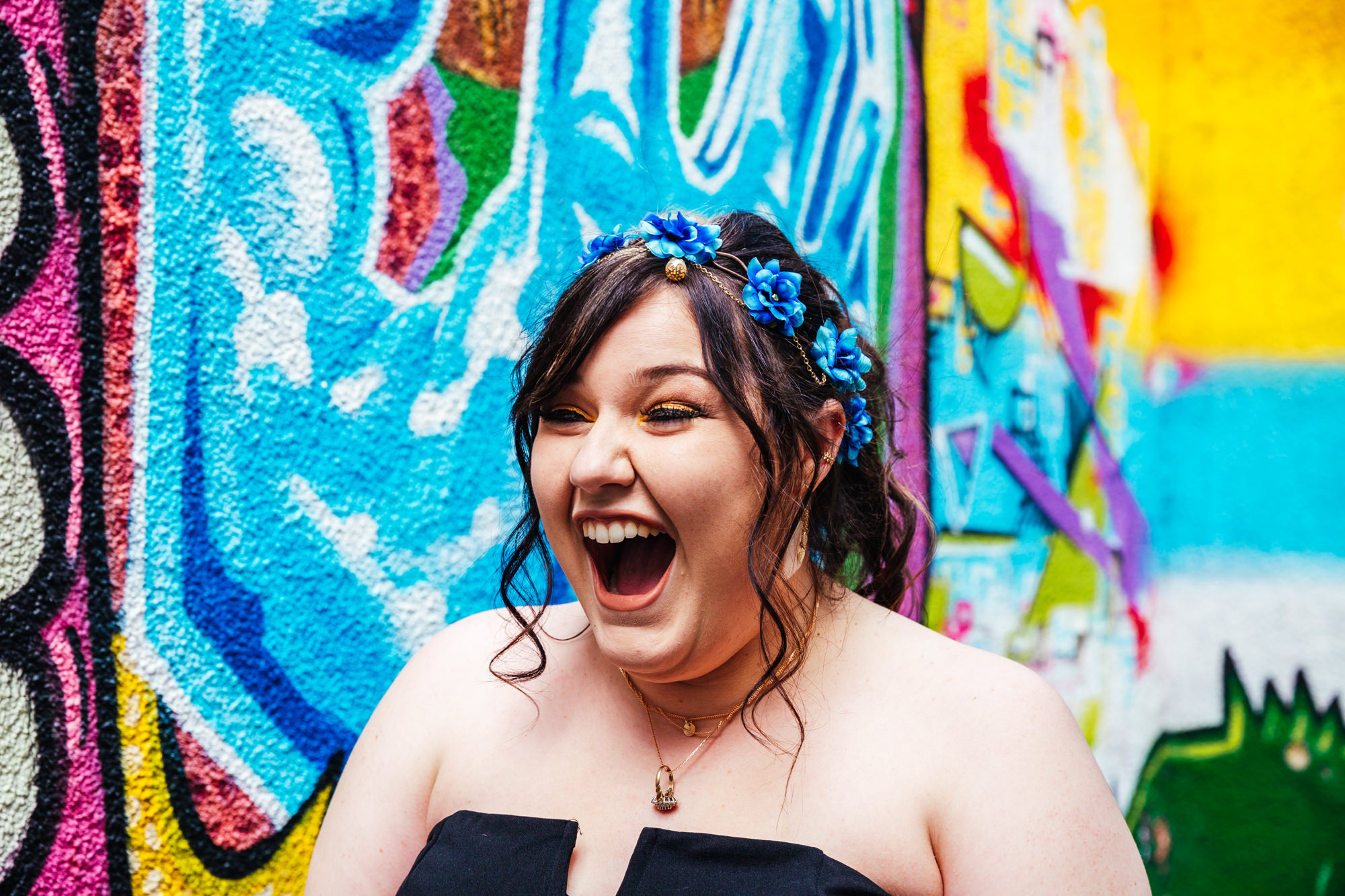 Wedding Photography Nottingham - Bride laughing standing by graffiti