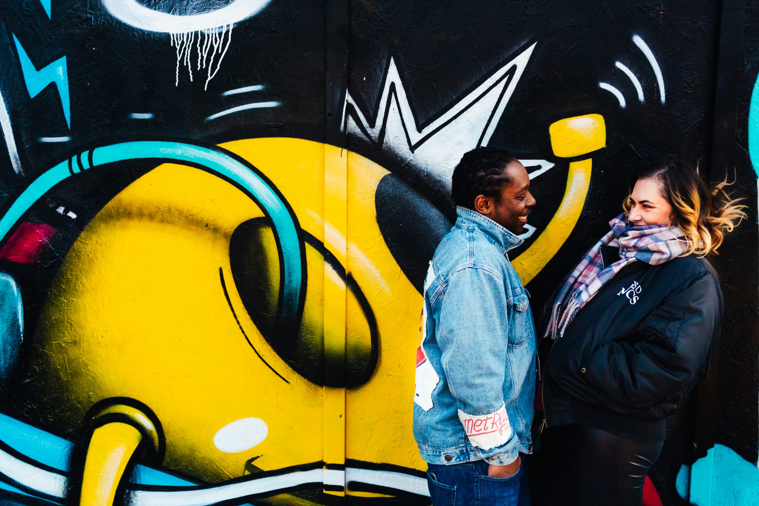 Fun engagement shoot - Couple in front of graffiti wall laughing together