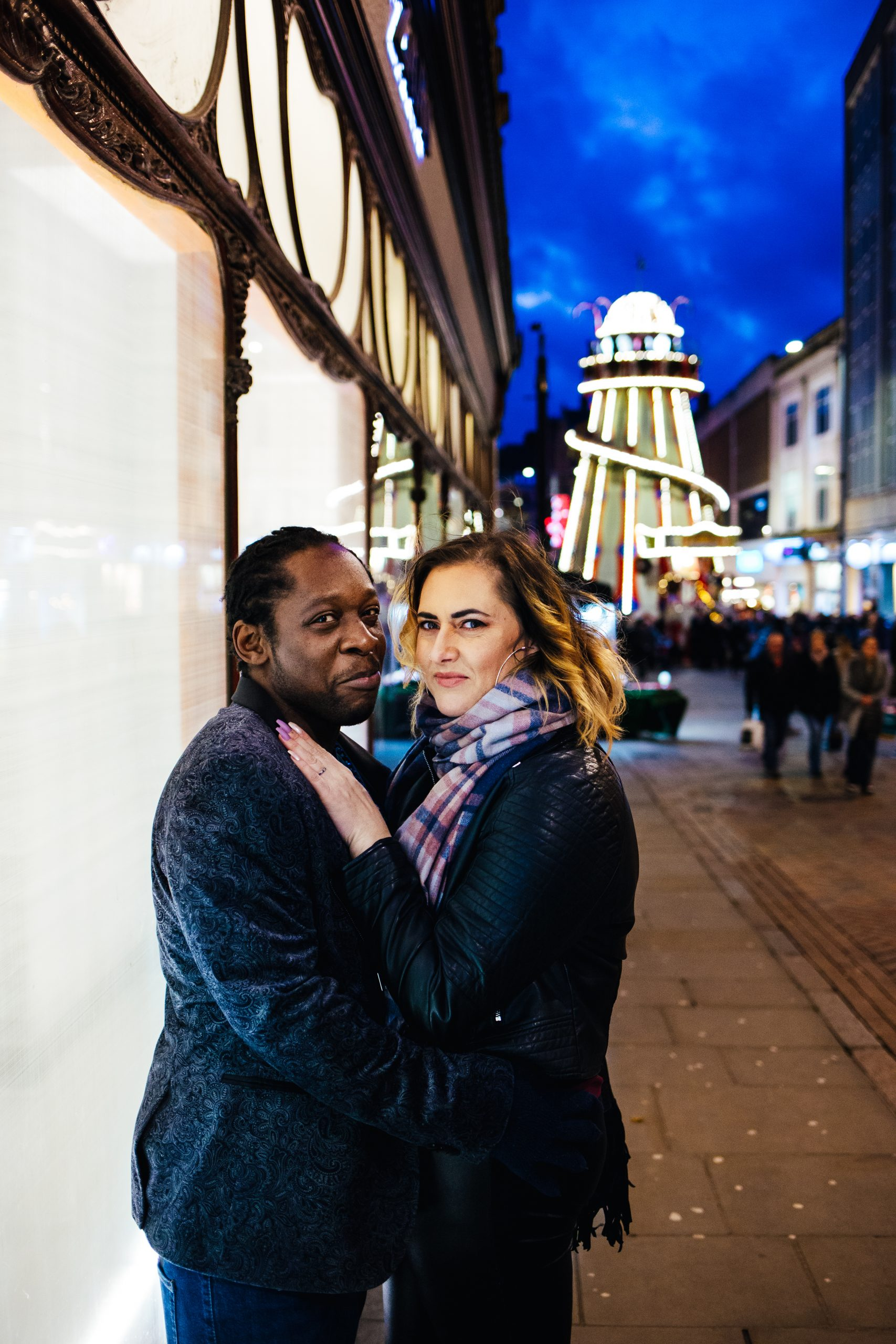 Fun Engagement Shoot - Couple lit by shop window during engagement shoot with fairground in the background