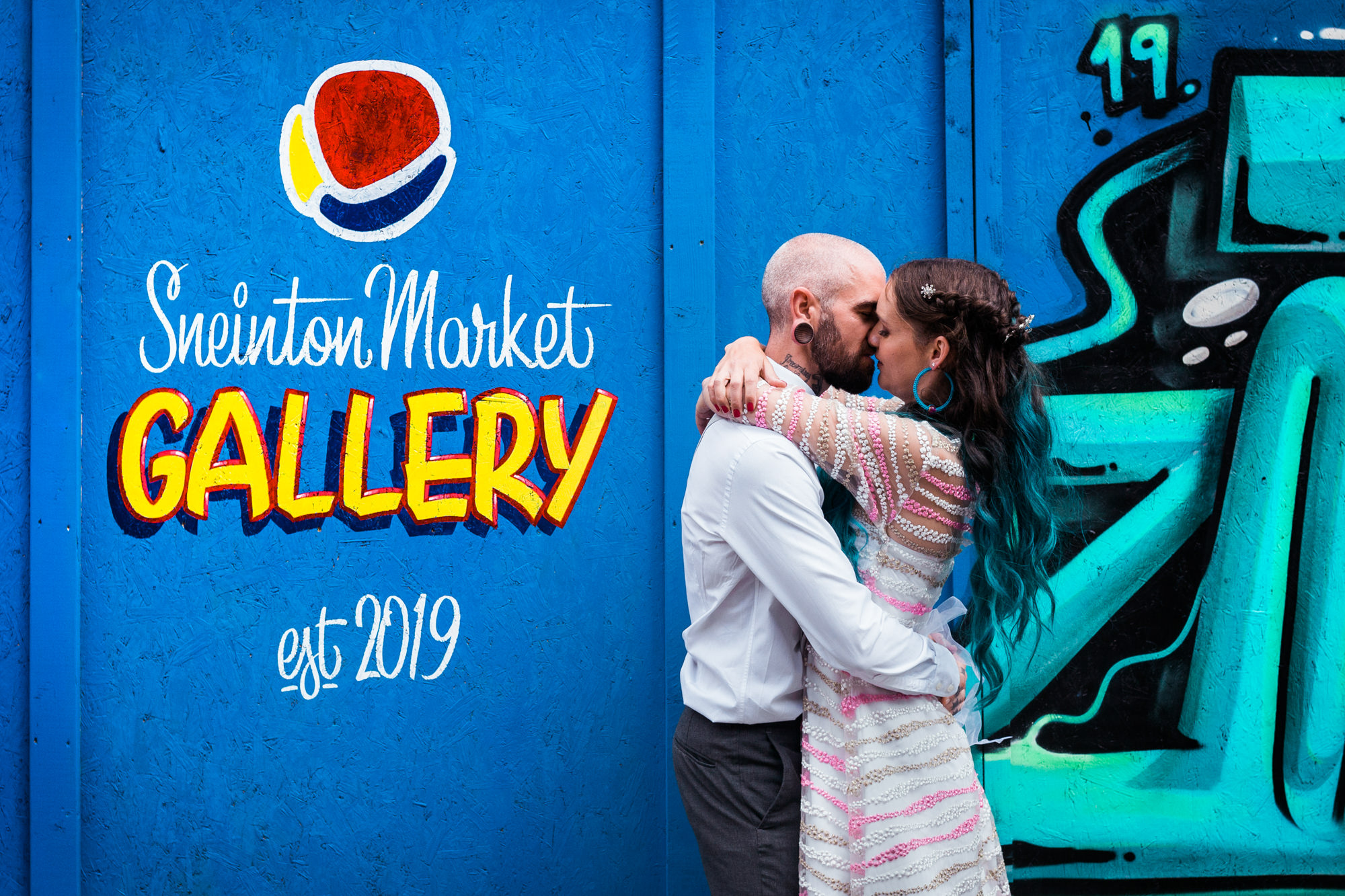 Wedding Planning - Couple stood in front of blue graffiti wall