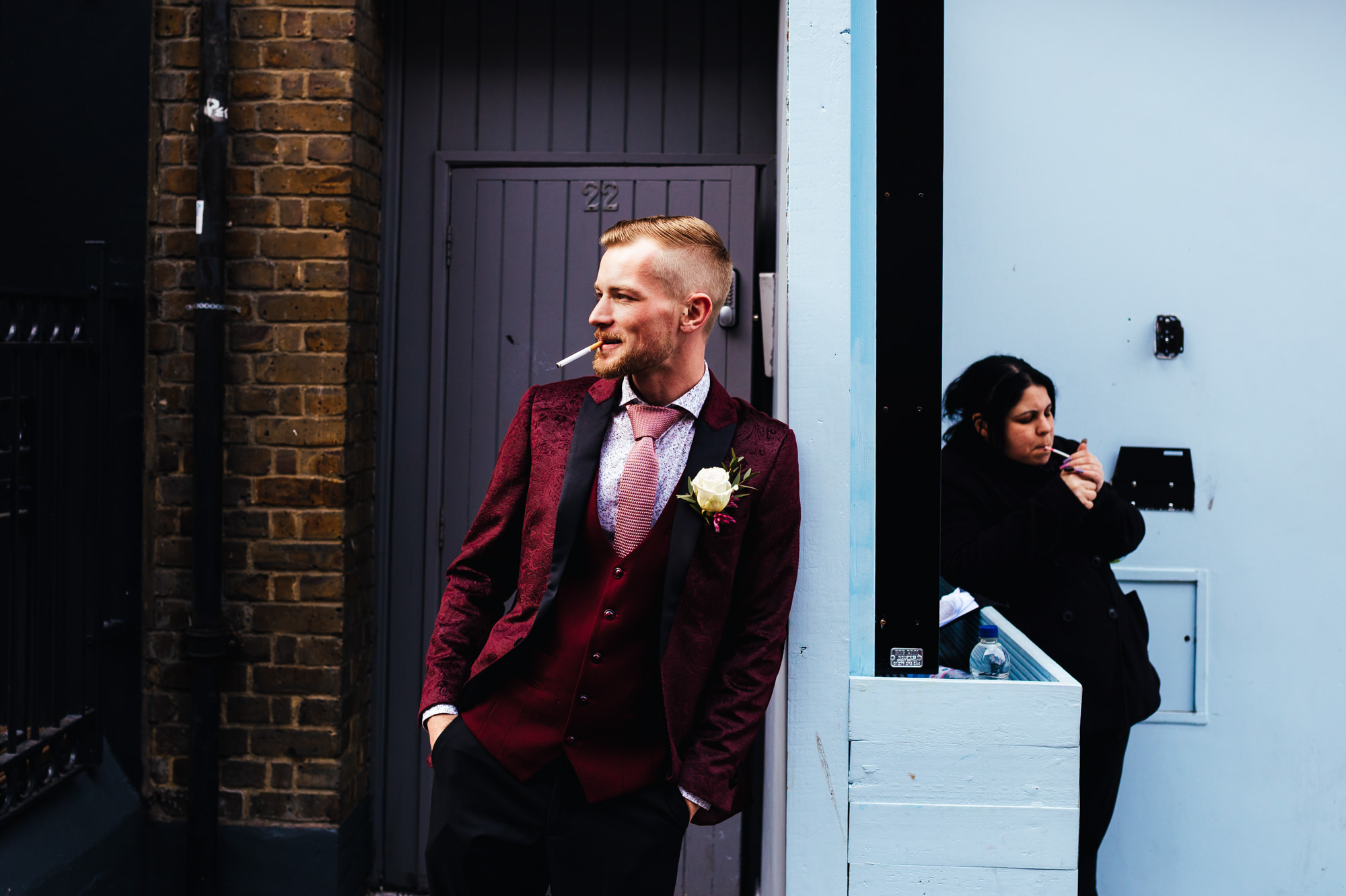 Groom smoking before leaving for wedding with member of the public mirroring him behind blue wall