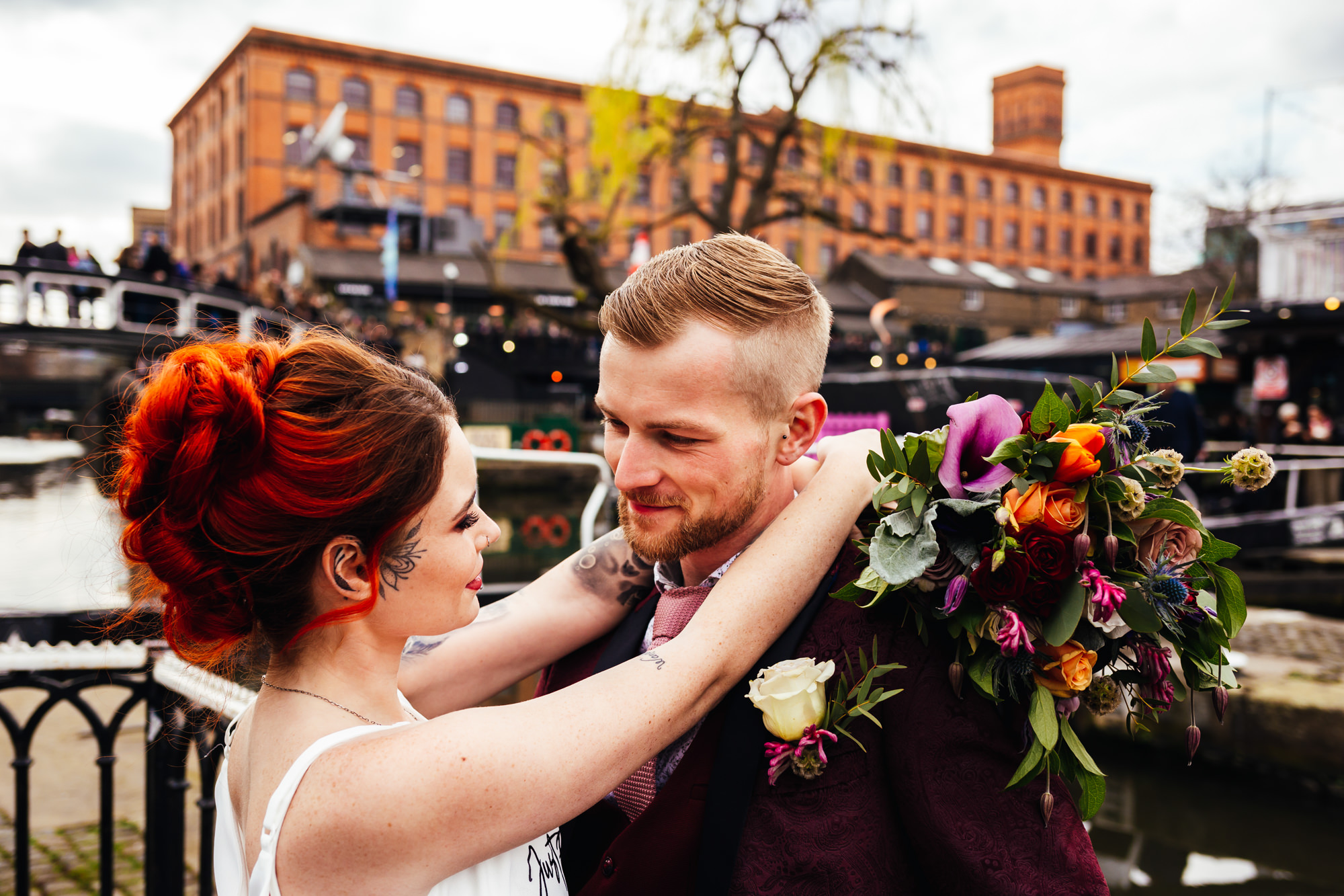 City Micro-Elopement - Couple in the centre of Camden town after wedding bride has arms around groom with bouquet in her hand
