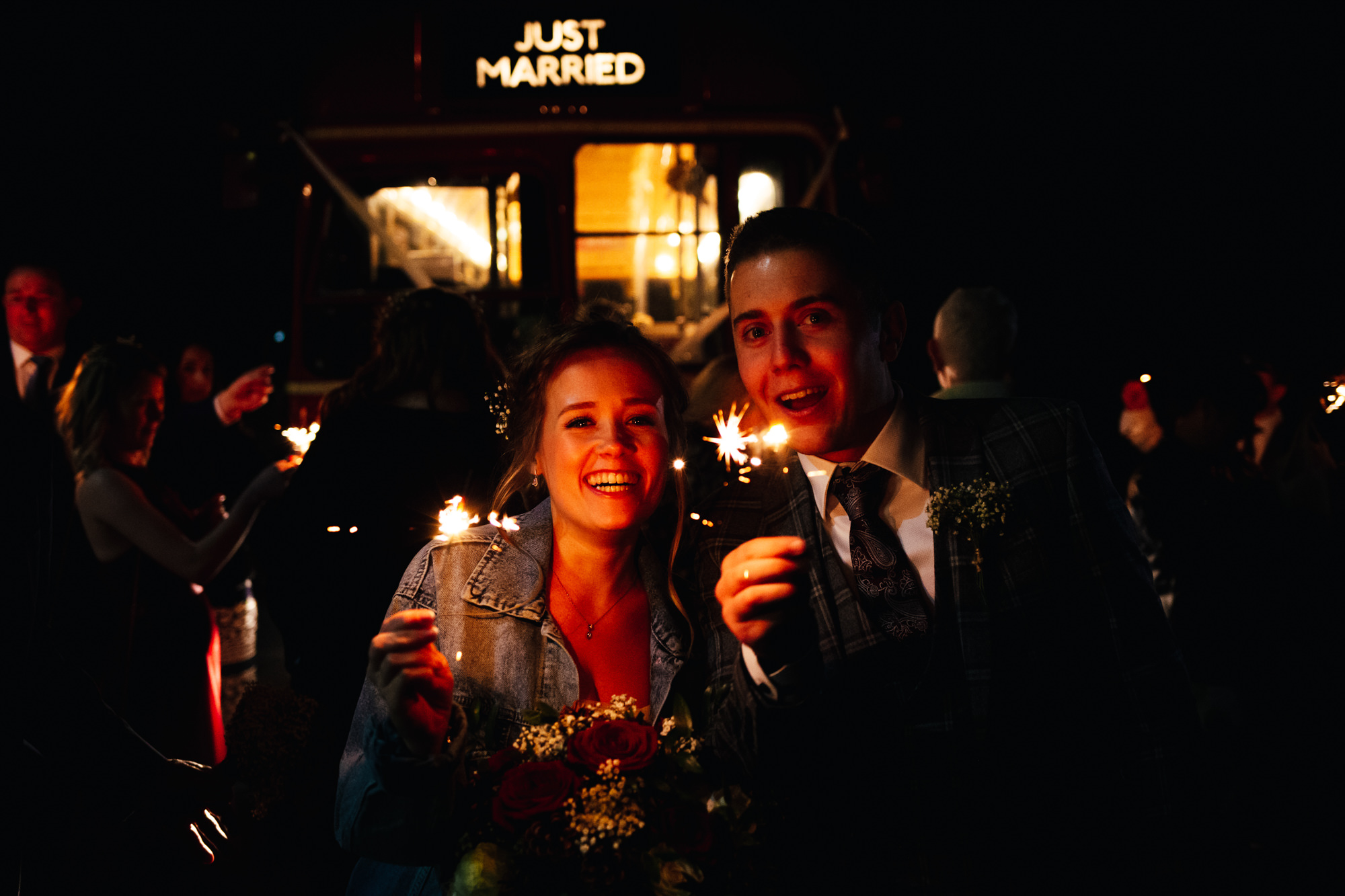 Couple holding sparklers on wedding day