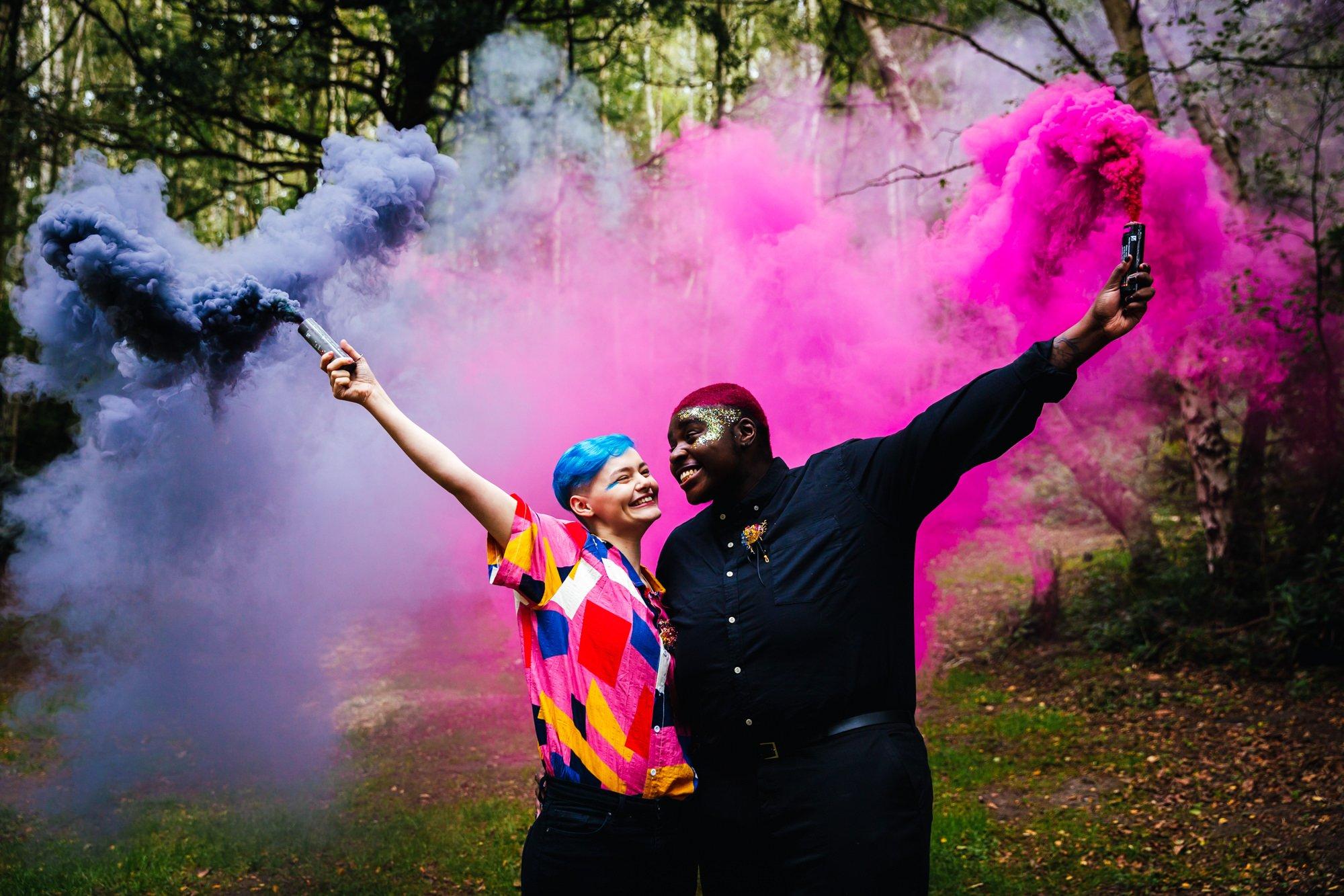 Wedding Smoke Bombs - Couple with pink and black smoke bombs at woodland wedding venue
