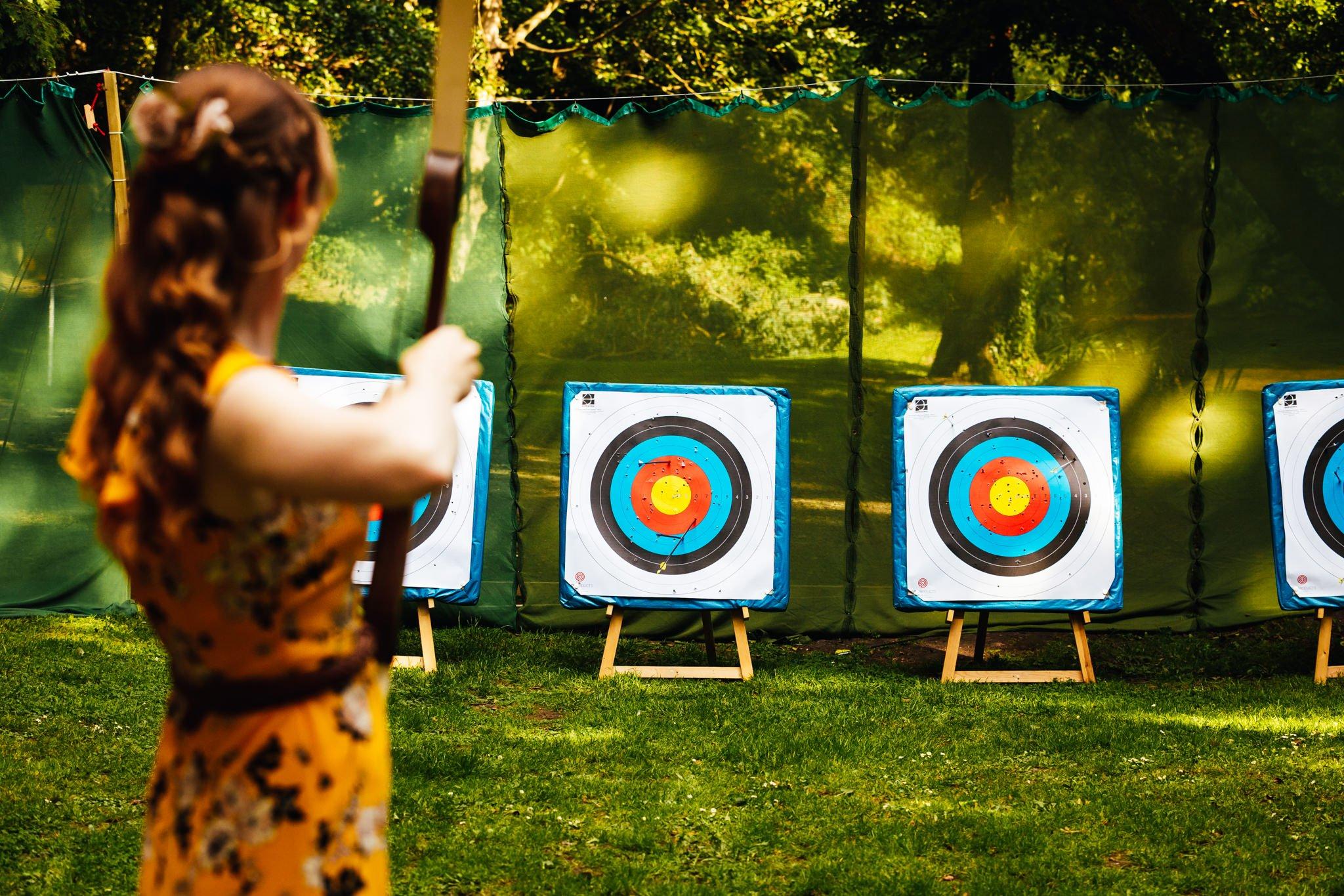 Outdoor Summer Wedding - Girl doing archery at wedding