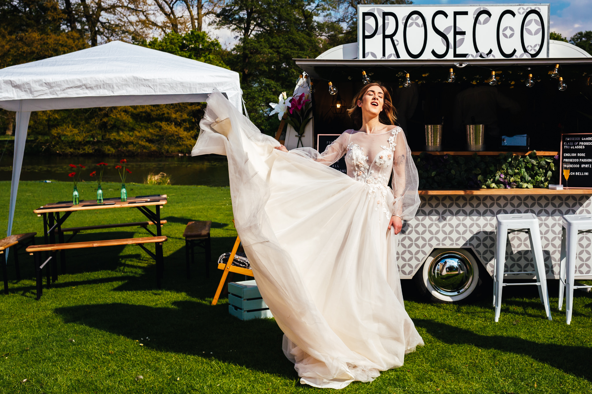 Outdoor Summer Wedding - Bride swishing in dress in front of prosecco