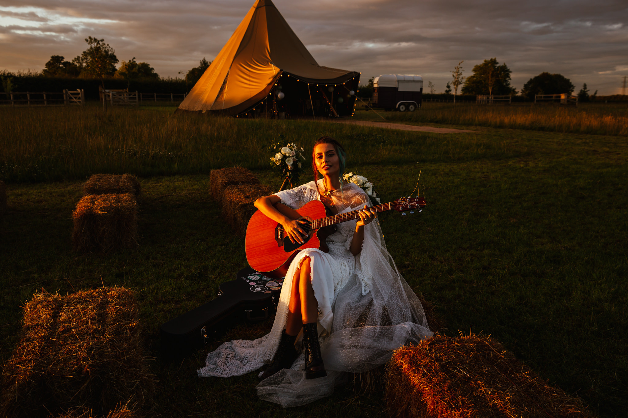 Outdoor Summer Wedding - Bride sat in front of Tipi playing guitar