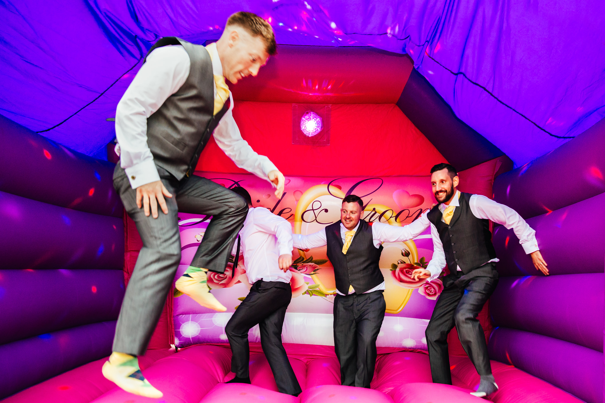 Wedding Entertainment - Groom & Groomsmen on pink bouncy castle having the time of their lives at wedding