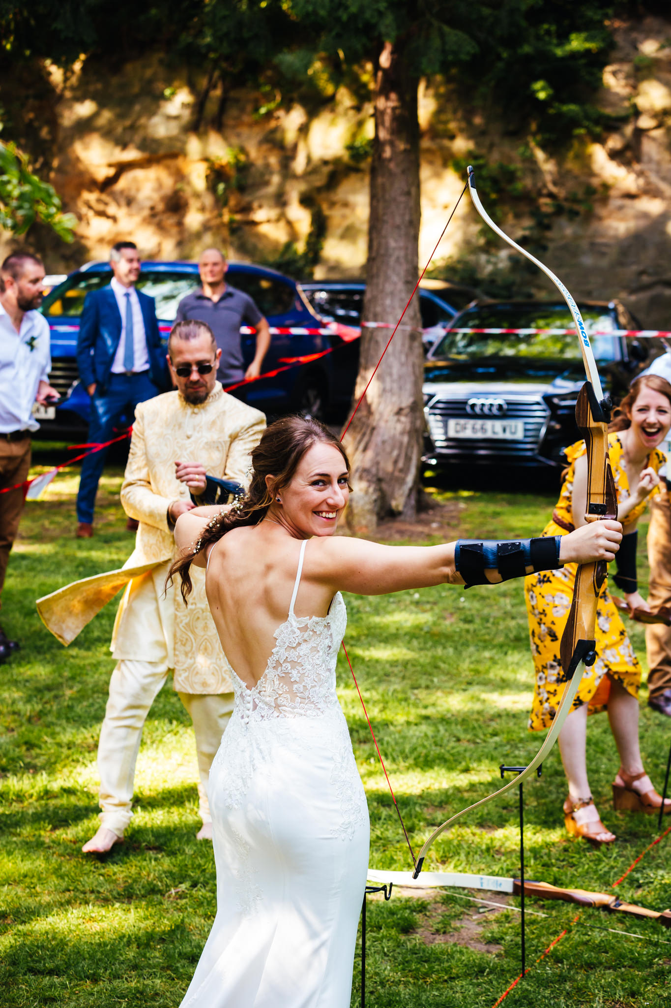 Wedding Entertainment - Bride doing archery at wedding in her dress