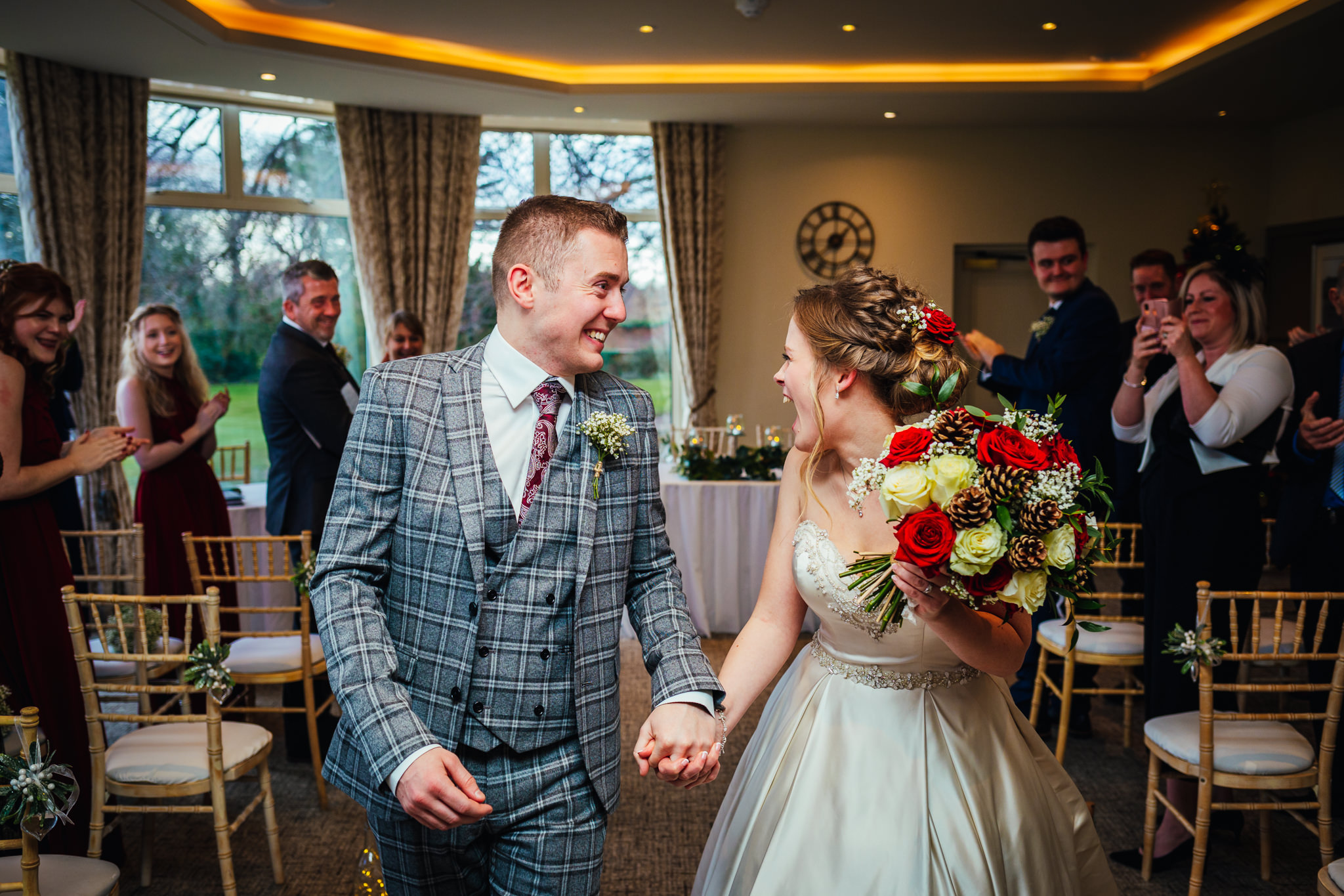 Wedding Photography Nottingham - Couple walking up the isle after wedding smiling at guests