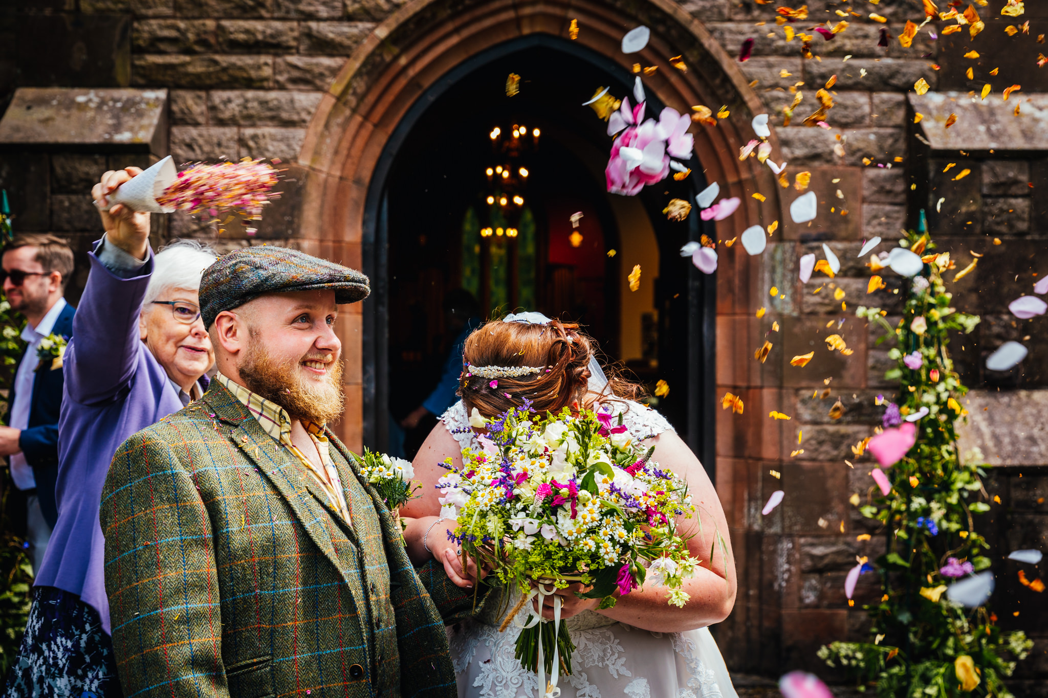 Wedding Photography Nottingham - Bride hiding behind her gorgeous summer bouquet whist having confetti thrown at her.
