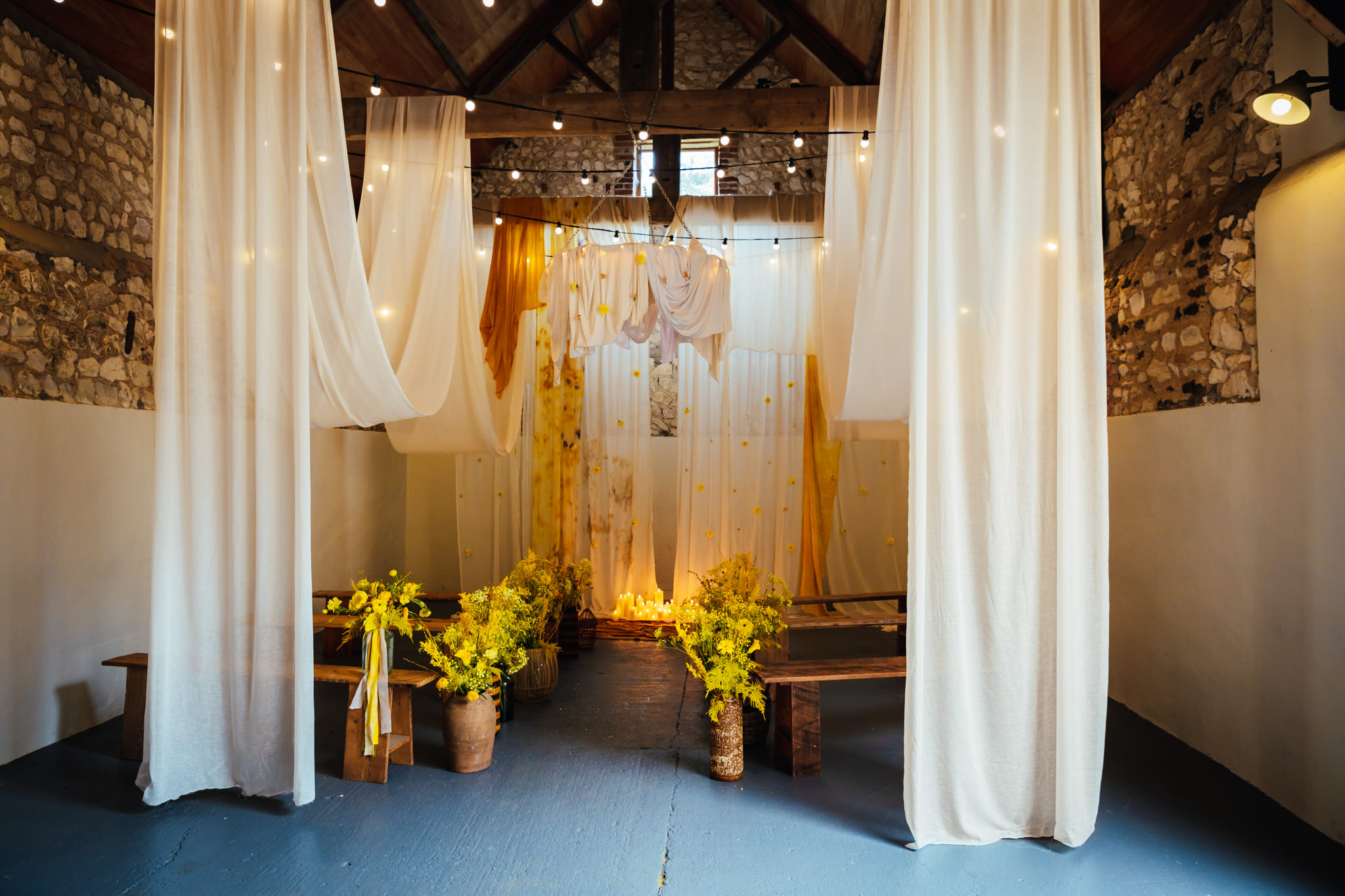 Happy Valley Norfolk - Ceremony Barn dressed for wedding in neutral colours with candles and yellow flowers