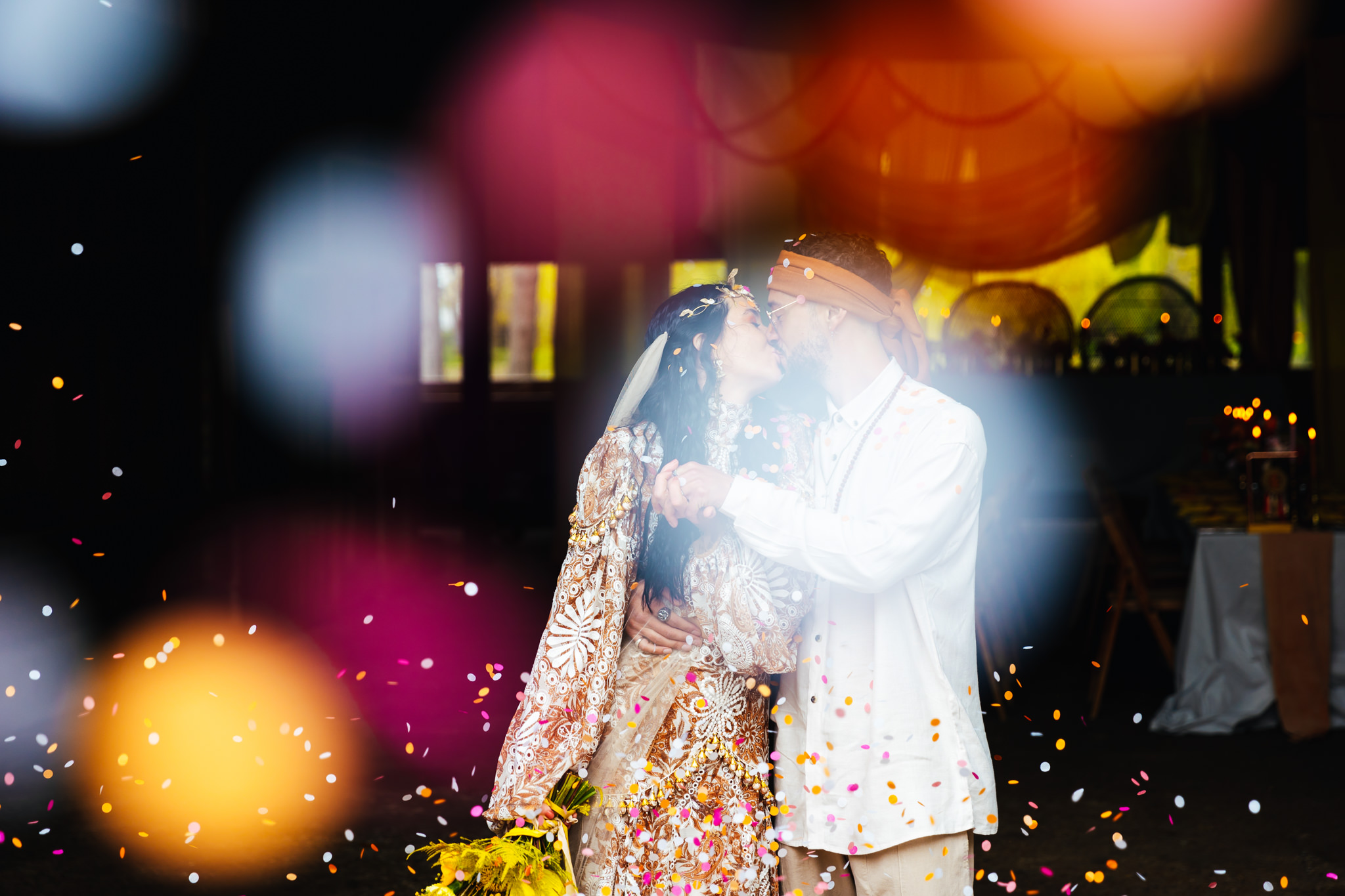 Happy Valley Norfolk - Couple during their confetti shot, confetti is brightly coloured and they're sharing a kiss