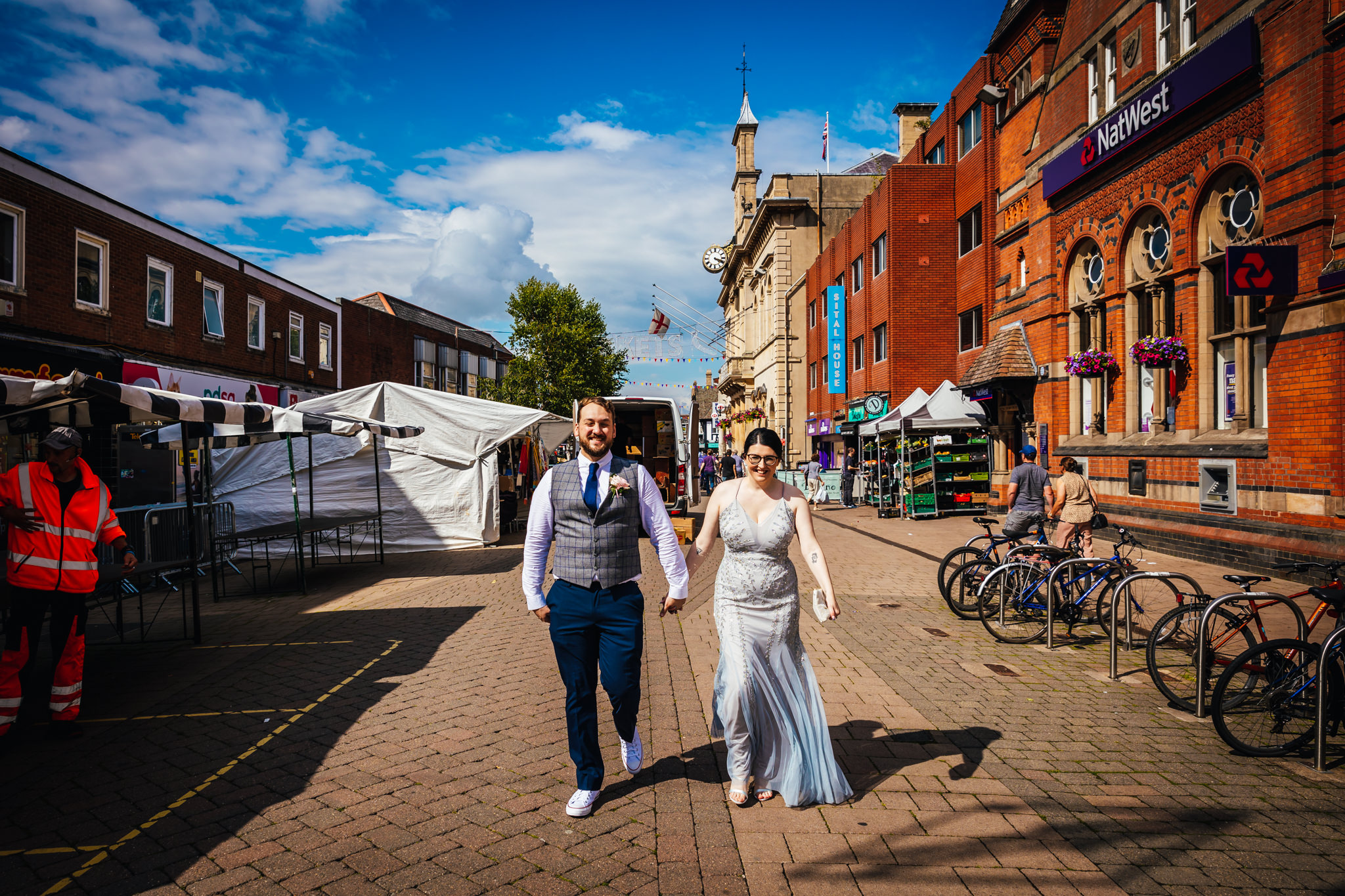 fun wedding photography - Couple walking through town centre on their wedding day. Bride is wearing grey dress and groom is relaxed in converse