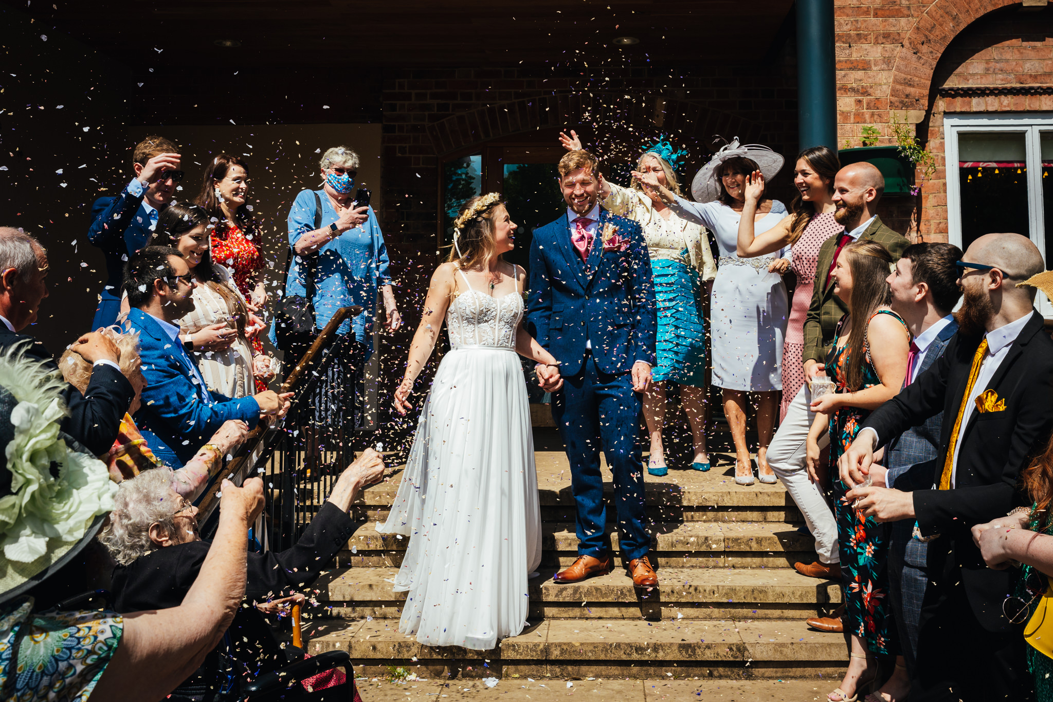 Fun Wedding Photography - Couple during confetti shoot at venue bride is in a beautiful dress groom is dress in blue