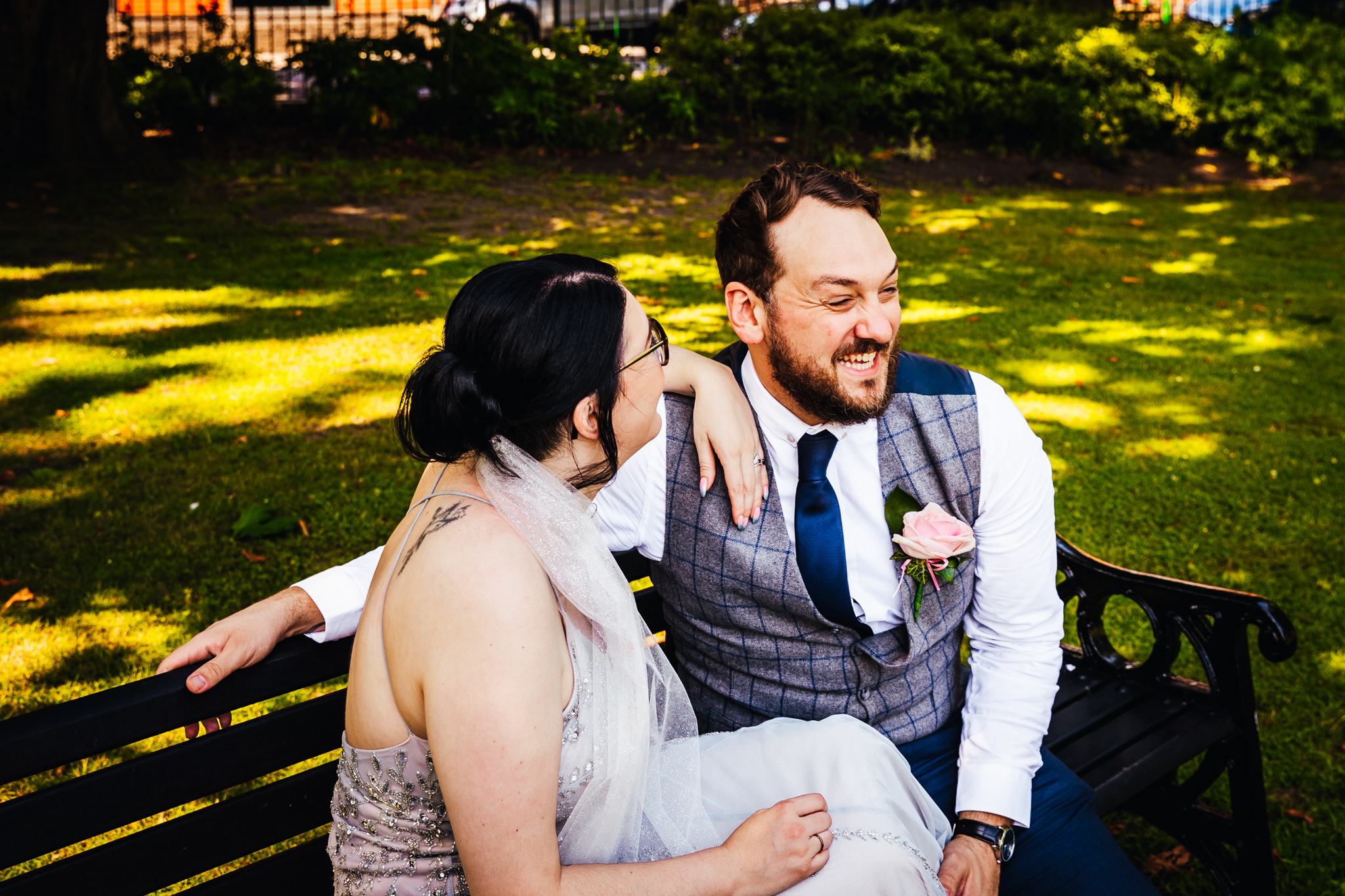 Wedding Photography Nottingham Bride and groom sat on a bench laughing together after ceremony