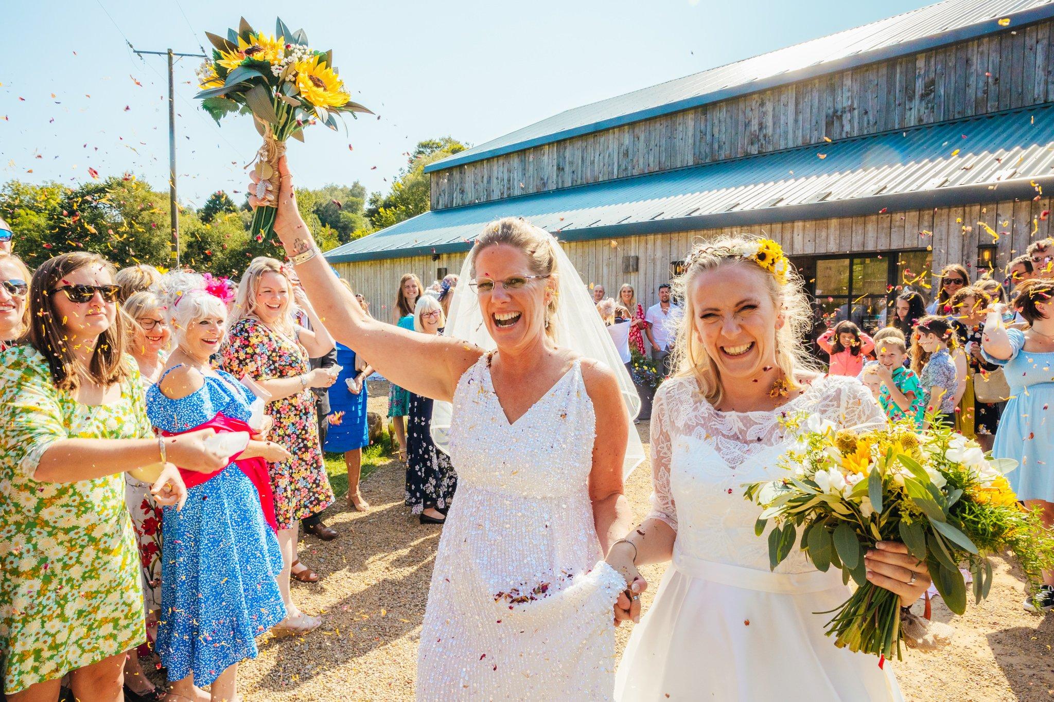Wedding Photography Nottingham - Brides walking through confetti tunnel on bright sunny day